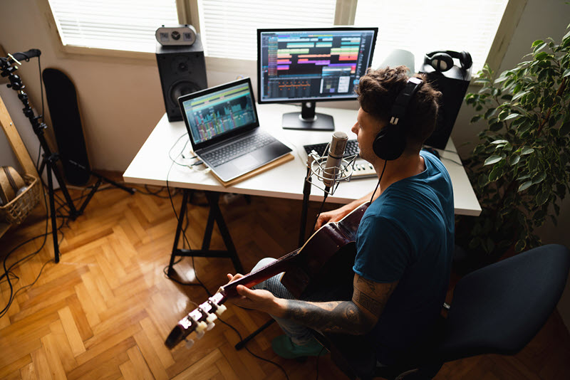 Young man playing guitar in home studio.